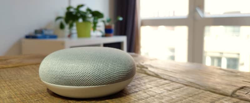 A Google Home sits on a table in a home